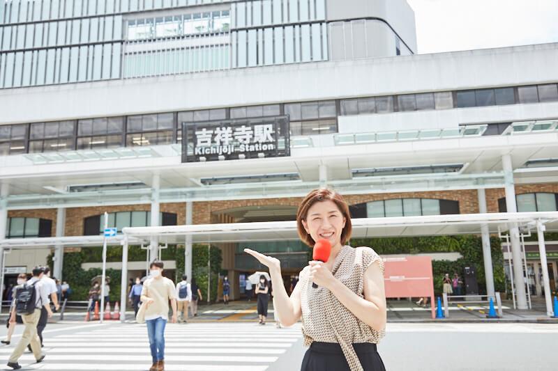 吉祥寺駅前でレポートする女性