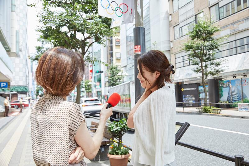 インタビューを受けるカーディガンを羽織った女性