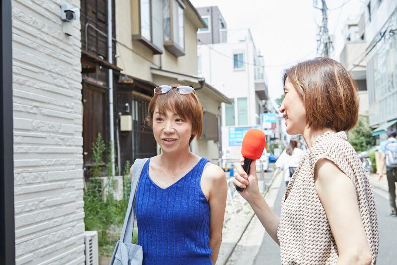 インタビューを受けるタンクトップの女性