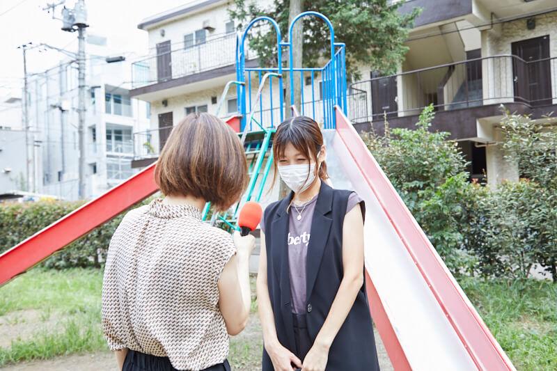 インタビューを受けるマスク姿の女性