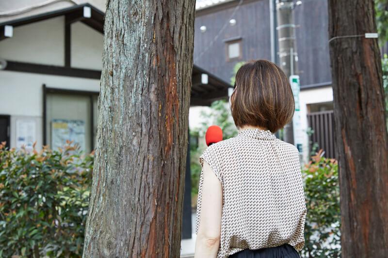 木の下でインタビューする女性